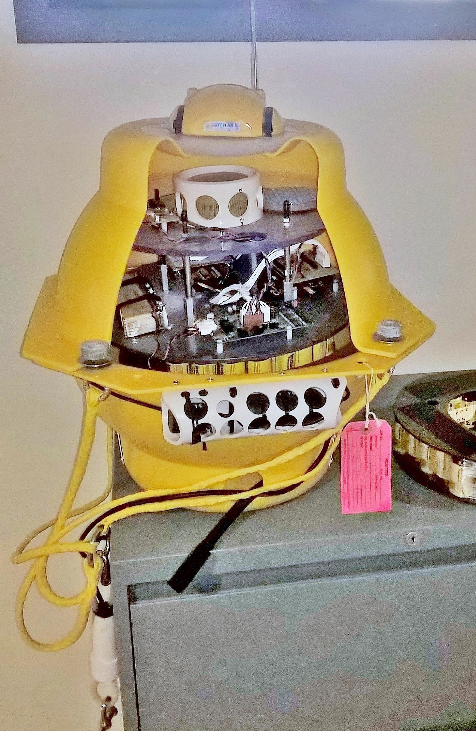 The ceramic hydrophone is stored in a white cradle to front side of the float. The float has been cut away to show the internal electronics and some of the battery storage.